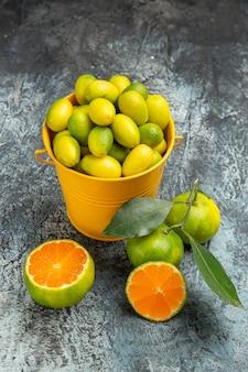Pionowy widok żółtego wiadra pełnego świeżych zielonych mandarynek i pokrojonych na pół mandarynek na szarym tle materiału