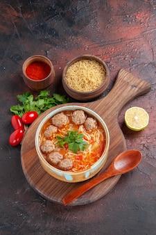 Pionowy widok zupy pomidorowej z klopsikami z makaronem w brązowej misce i różnymi przyprawami na ciemnym tle