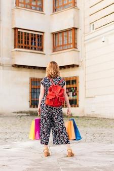 Pionowy wizerunek kobiety od tyłu z kolorowymi torebkami w dłoniach podczas zakupów na wyprzedaży.