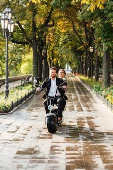 Pionowy wizerunek szczęśliwej eleganckiej pary jedzie na nowożytnym motocyklu