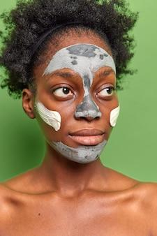 Pionowy wizerunek zamyślonej, kręconej kobiety, która odwraca wzrok, ma duże oczy pełne usta nakłada na twarz odżywczą maskę glinianą, aby usunąć pory i drobne zmarszczki pozuje bez koszuli na zieloną ścianę