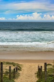 Pionowy wysoki kąt strzału drogi z drewnianymi balustradami prowadzącymi do morza