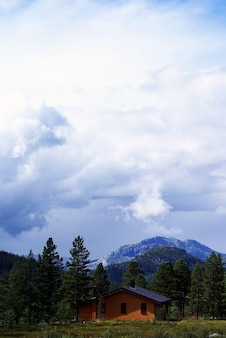 Pionowy wysoki kąt strzału małego domu na wzgórzach pod zachmurzonym niebem w tuddal gaustatoppen