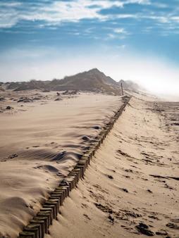 Pionowy wysoki kąt strzału piaszczystej ziemi pod jasnym pochmurnym niebem