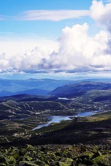 Pionowy wysoki kąt strzału wzgórz pod zachmurzonym niebem w tuddal gaustatoppen, norwegia