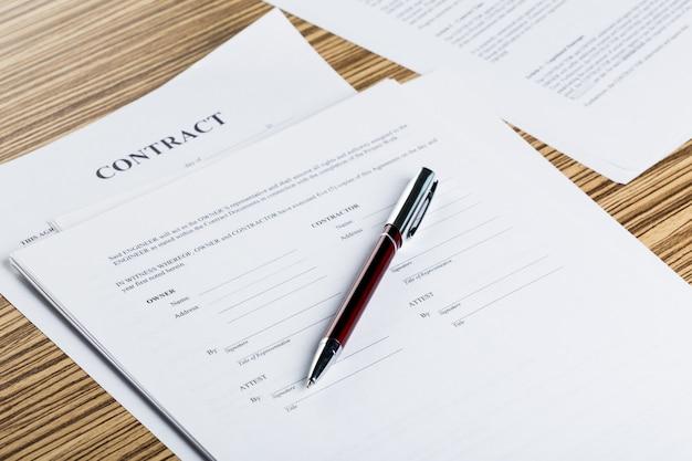 Pióra i dokumenty kontraktowe na drewnianym biurku