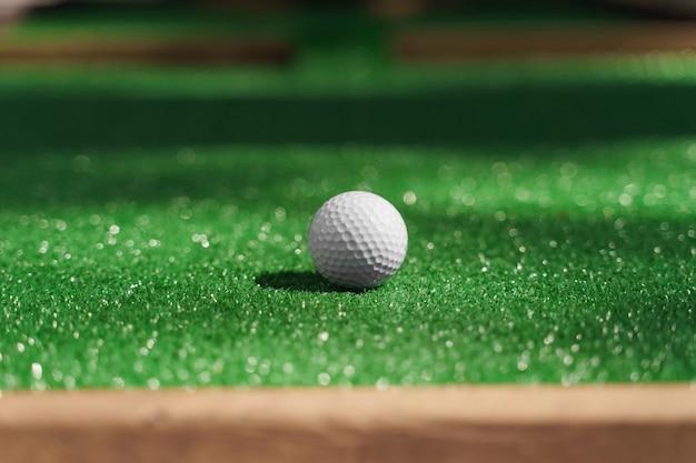 Piórkowa piłka do golfa na zielonej trawie w słoneczny dzień