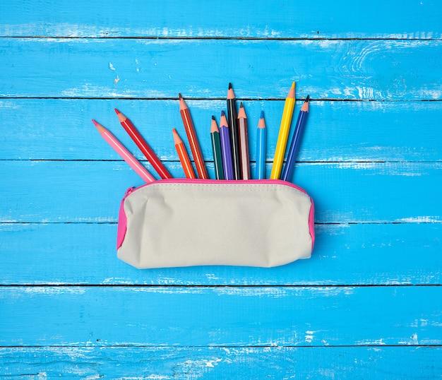 Piórnik szkolny szary tekstylny i rozrzucone wielokolorowe drewniane ołówki