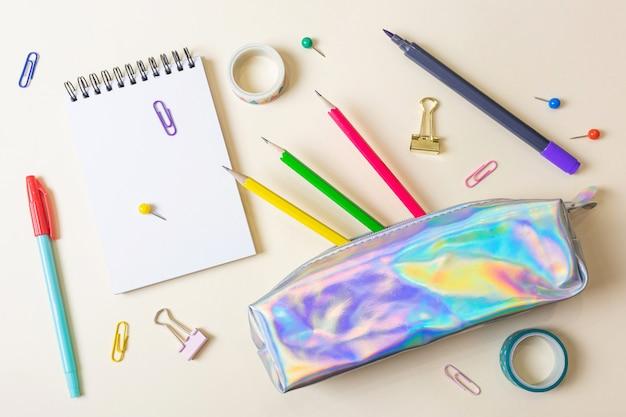Piórnik z długopisami i ołówkami, notatnik. miejsce na tekst, minimalizm. koncepcja papeterii dla szkoły, biura, edukacji.