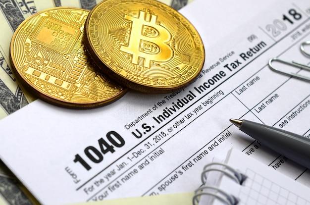 Pióro, bitcoiny i banknoty dolarowe leżą na formularzu podatkowym 1040 us indywidualny zwrot podatku dochodowego. czas płacić podatki