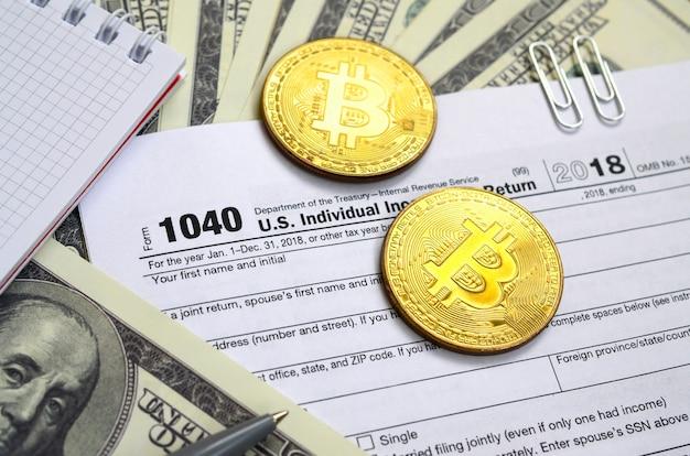 Pióro, bitcoiny i banknoty dolarowe leżą na formularzu podatkowym 1040 us