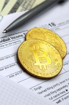 Pióro, bitcoiny i banknoty dolarowe leżą na formularzu podatkowym 1040
