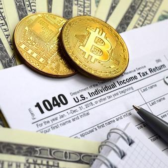 Pióro, bitcoiny i banknoty dolarowe leżą na formularzu podatkowym