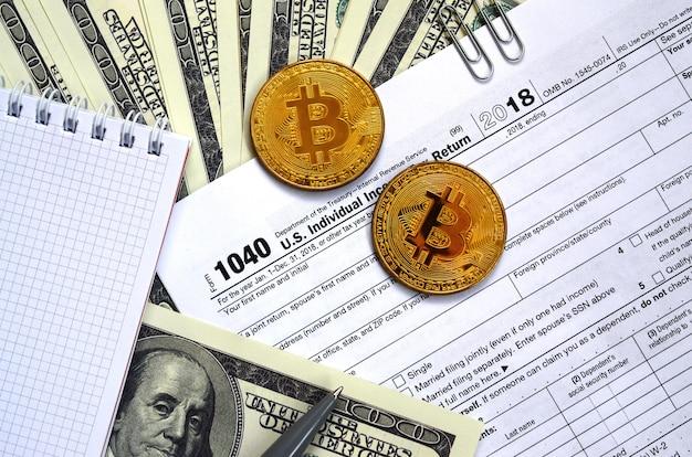 Pióro, bitcoiny i banknoty dolarowe leżą w formularzu podatkowym 1040 us indywidualny zwrot podatku dochodowego. czas płacić podatki