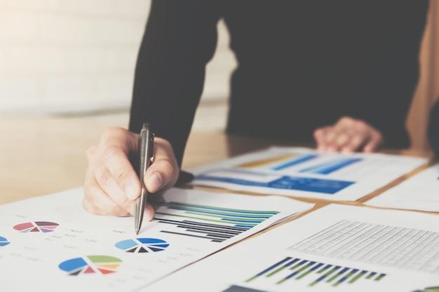 Pióro bizneswoman wskazuje wykres wykresu w tym miesiącu dla planów poprawy jakości w przyszłym miesiącu.