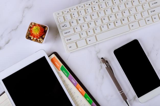 Pióro, cotygodniowy notatnik, telefon komórkowy, cyfrowy tablet i klawiatura komputerowa
