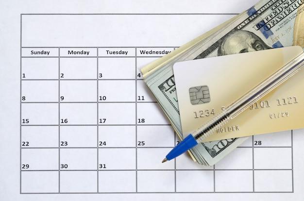 Pióro i karta kredytowa na wieluset rachunkach w dolarach amerykańskich na stronie kalendarza z bliska