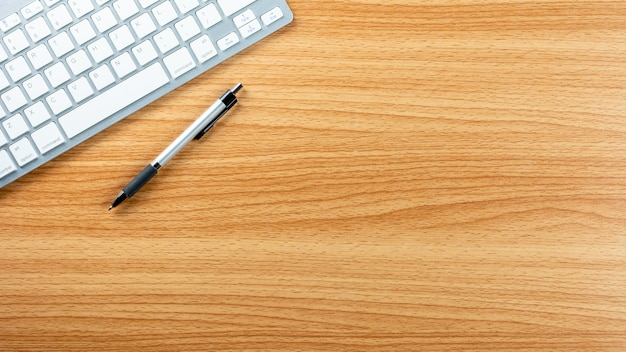 Pióro i komputerowa klawiatura na drewnianym biurka tle.