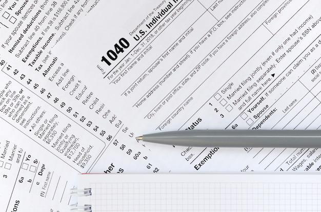 Pióro i notatnik leżą na formularzu podatkowym 1040 zwrot podatku dochodowego w usa