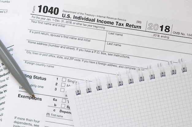 Pióro i notatnik leży na formularzu podatkowym 1040 us indywidualny zwrot podatku dochodowego. czas płacić podatki