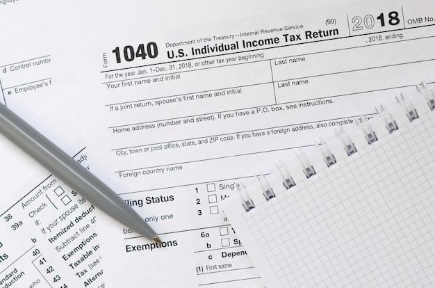 Pióro i notatnik leży na formularzu podatkowym 1040 usa