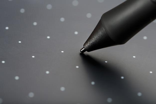 Pióro i tablet graficzny zbliżenie na szarym tle tekstury. gadżet do pracy jako projektant, artysta i fotograf.