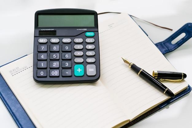Pióro, kalkulator i notatnik na białych stołowych tło ,.