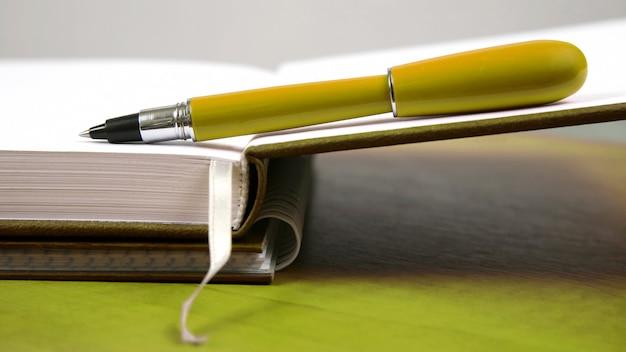 Pióro leżące na otwartym zeszycie. przedmioty dla biznesu i edukacji