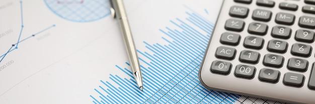Pióro leży na niebieskiej wykresie statystyk finansowych