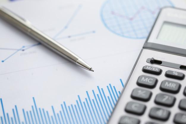 Pióro leży na niebieskiej wykresie statystyk finansowych.