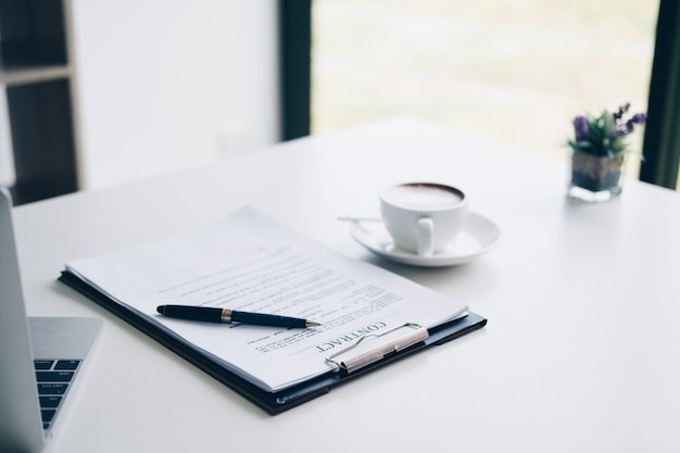 Pióro na arkuszu umowy i dokumencie biznesowym