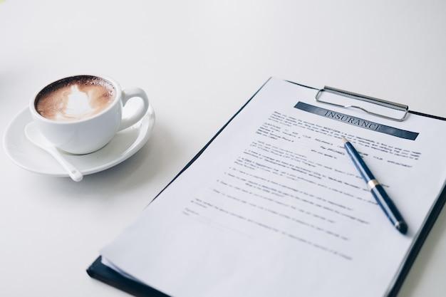 Pióro na arkuszu umowy ubezpieczenia i dokument biznesowy, w pobliżu filiżanki kawy