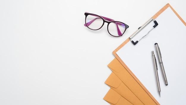 Pióro na kopercie na dokumenty i tablicy oraz okularach na blacie stołu widok miejsca kopiowania