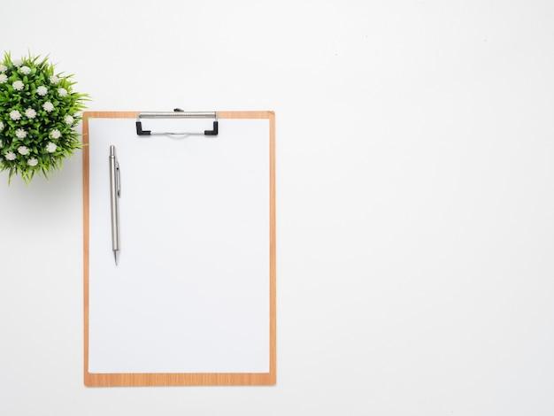 Pióro na tablicy dokumentów z wazonem na widoku z góry na miejsce na stół