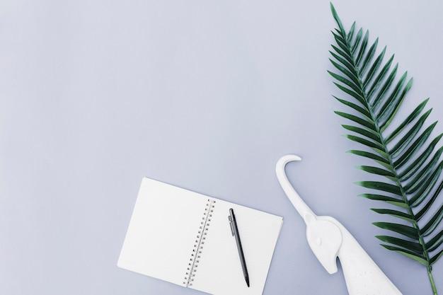 Pióro nad notatnikiem, białą jednorożec i liściem na białym tle ,.