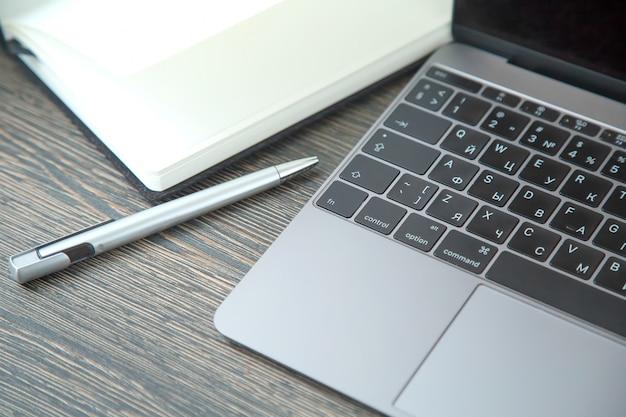Pióro, notatnik i notatnik z klawiaturą na drewnianym stole