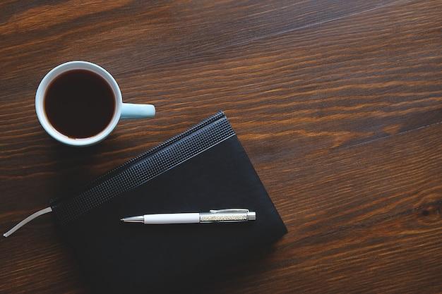 Pióro, notatnik lub pamiętnik, filiżanka herbaty lub kawy na drewnianym stole.