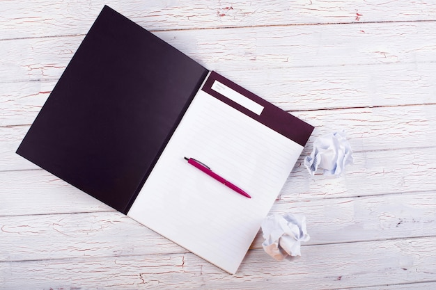 Pióro, notesy i papiery stoją na stole