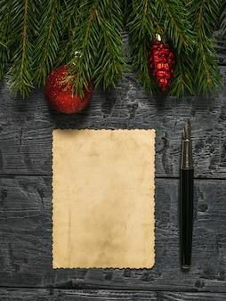 Pióro wieczne, kartka starego papieru, ozdoby i świerkowe gałązki na drewnianym tle. list z prośbą o prezent.