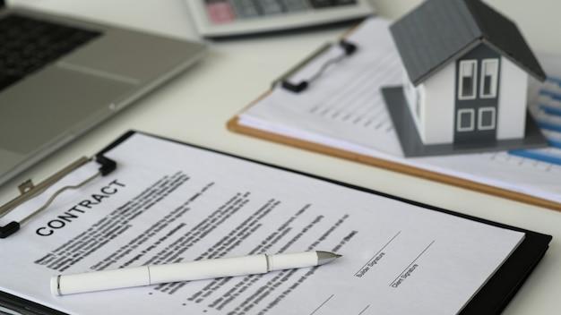 Pióro z dokumentami do podpisania umowy o budowę domu z modelowym domem i laptopem, koncepcja nieruchomości, zbliżenie strzał.