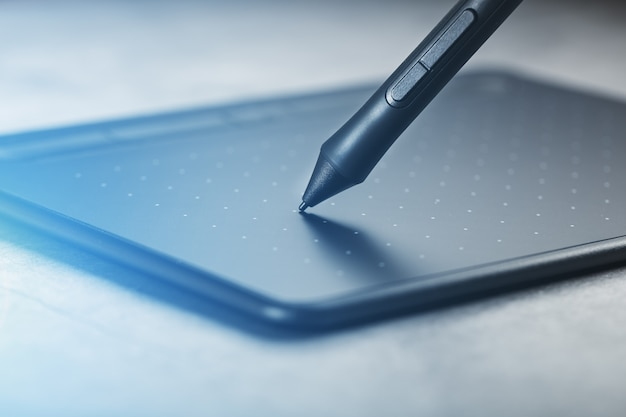 Pióro z tabletem graficznym w rękach projektanta, zbliżenie. gadżet do sztuki i pracy.