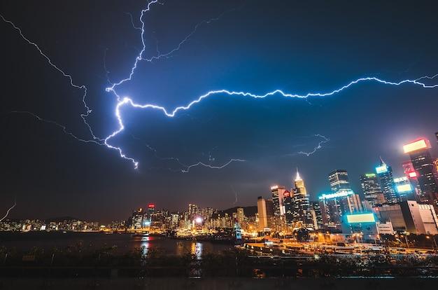 Piorun uderza nocą w nowoczesne miasto miejskie