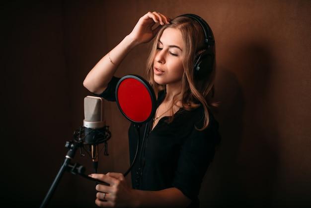 Piosenkarka nagrywa piosenkę w studio muzycznym. kobieta wokalistka w słuchawkach przed mikrofonem.