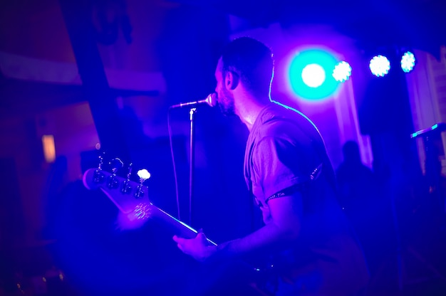 Piosenkarka pod kolorowymi światłami podczas występu na żywo