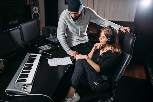 Piosenkarka słuchać nagrania piosenki w studio muzycznym