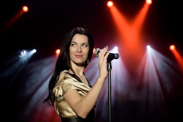 Piosenkarka w sukience na scenie w promieniach jasnego światła z dymem.