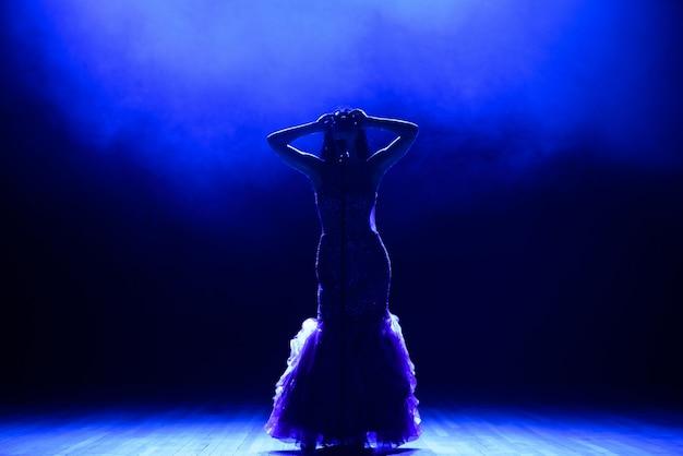 Piosenkarka w sylwetce. młoda kobieta piosenkarka na scenie podczas koncertu.