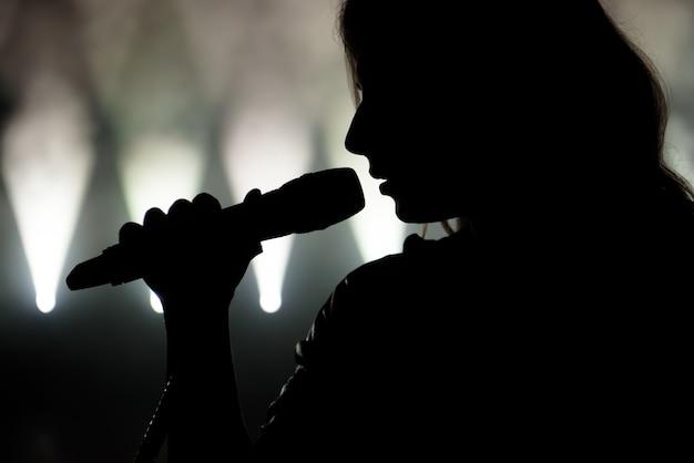 Piosenkarka w sylwetce. zamknij się obraz piosenkarki na żywo na scenie