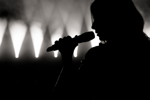 Piosenkarka w sylwetce. zamknij się obraz żywego piosenkarza na scenie