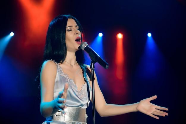 Piosenkarka z mikrofonem na kolorowej lekkiej scenie